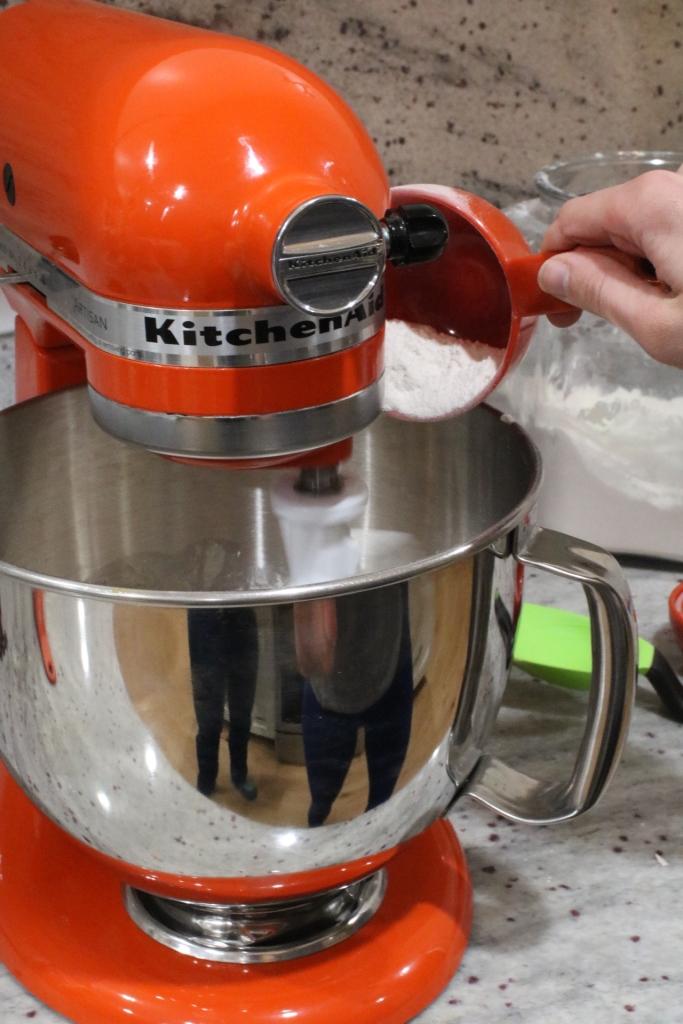 adding flour to mixer